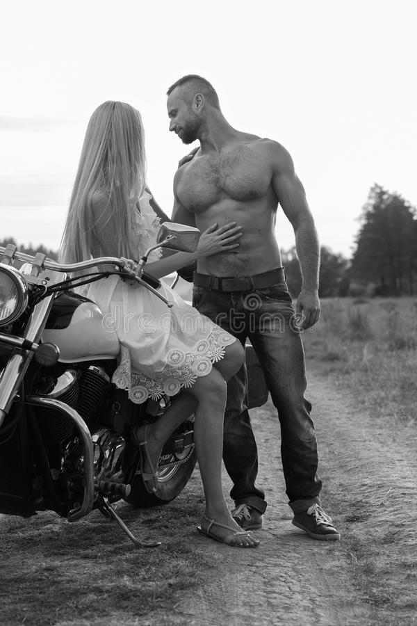 El individuo con la muchacha en un campo en una motocicleta imagenes de archivo