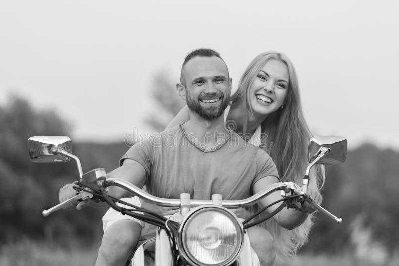 El individuo con la muchacha en un campo en una motocicleta imagen de archivo libre de regalías