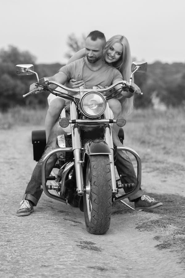 El individuo con la muchacha en un campo en una motocicleta fotos de archivo libres de regalías