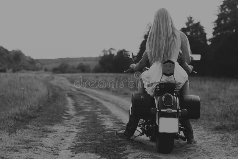 El individuo con la muchacha en un campo en una motocicleta foto de archivo libre de regalías