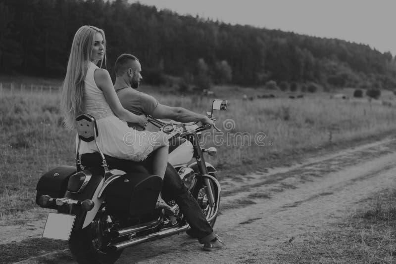 El individuo con la muchacha en un campo en una motocicleta fotografía de archivo libre de regalías