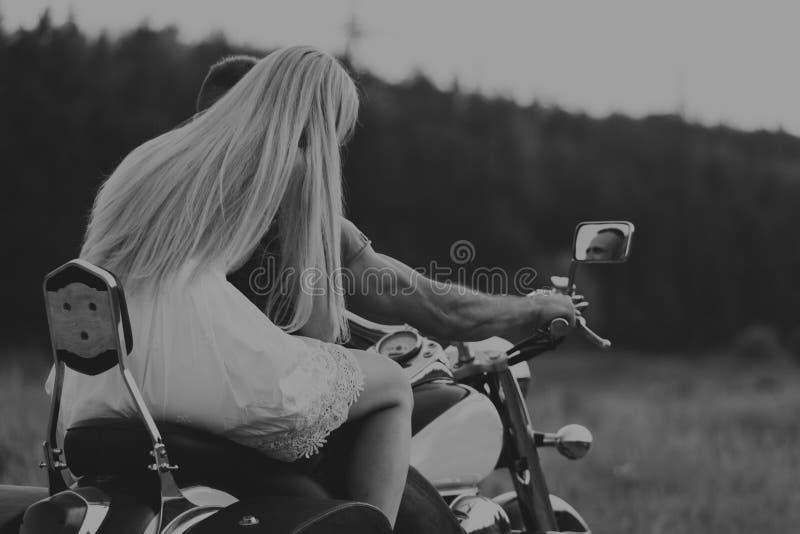 El individuo con la muchacha en un campo en una motocicleta foto de archivo