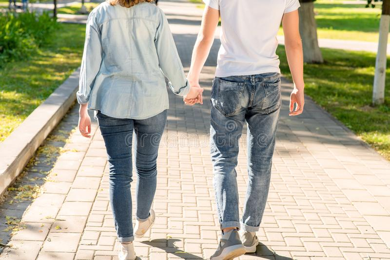 El individuo con la muchacha En verano en el parque en naturaleza Caminan a lo largo de la acera que se detiene las manos del ` s imagen de archivo