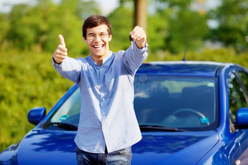 El individuo con llave del coche muestra el pulgar para arriba fotos de archivo libres de regalías