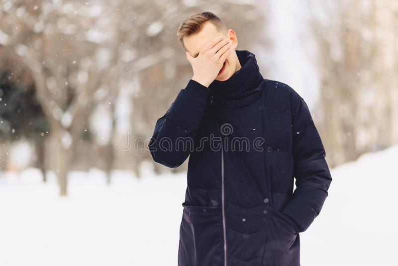 El individuo con el pelo corto ligero en una chaqueta del invierno hizo un facepalm imágenes de archivo libres de regalías