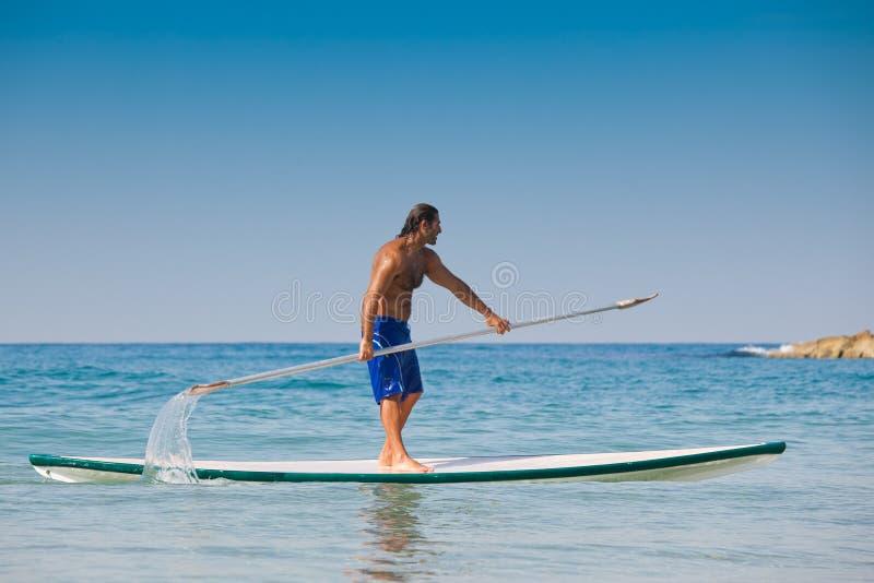 El individuo con un remo en una tabla hawaiana. foto de archivo