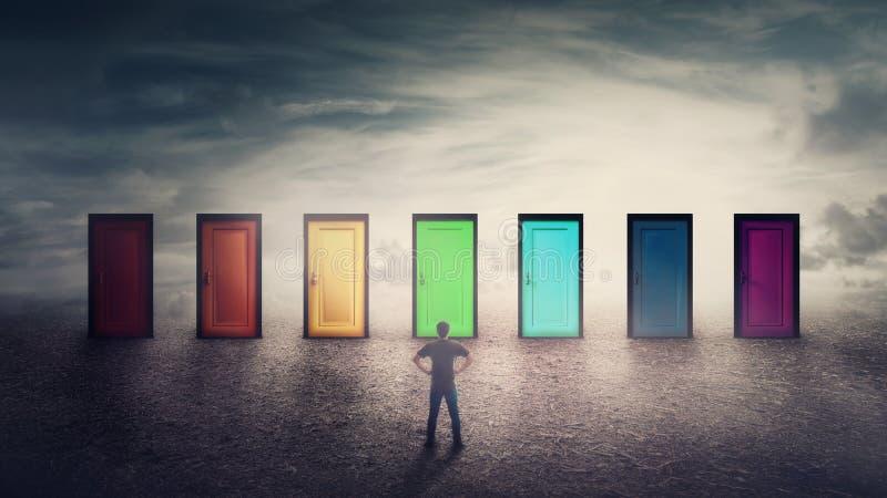 El individuo confiado delante de muchos diferentes de las puertas coloreado tiene que elegir uno imagenes de archivo