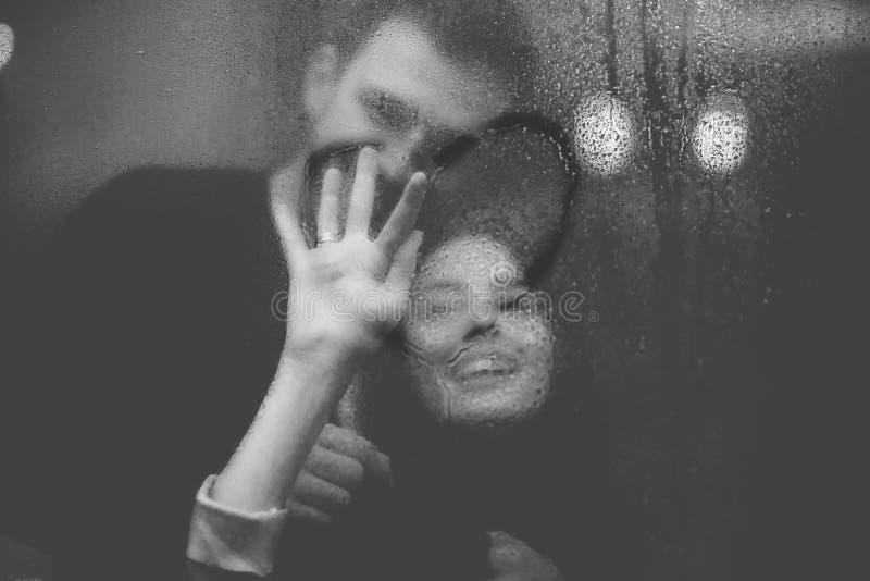 El individuo de amor abraza a su novia hermosa que dibuja un corazón sobre el vidrio misted foto de archivo libre de regalías