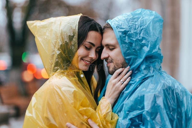 El individuo de amor y su novia en los impermeables se colocan cara a cara en la calle bajo la lluvia foto de archivo libre de regalías