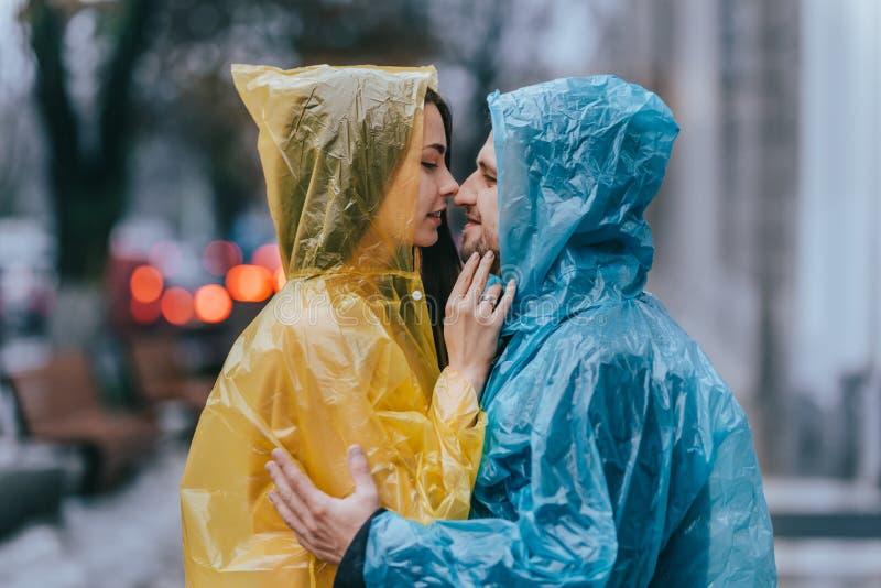 El individuo de amor y su novia en los impermeables se colocan cara a cara en la calle bajo la lluvia imagen de archivo libre de regalías