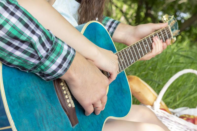 El individuo de la comida campestre del verano enseña a la muchacha a jugar dulzura caliente del amor de la guitarra imagenes de archivo