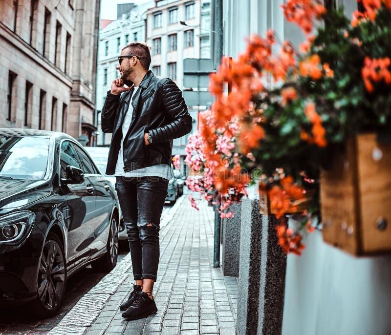 El individuo de moda en las gafas de sol vestidas en una chaqueta de cuero negra y vaqueros habla por un smartphone mientras que  fotografía de archivo