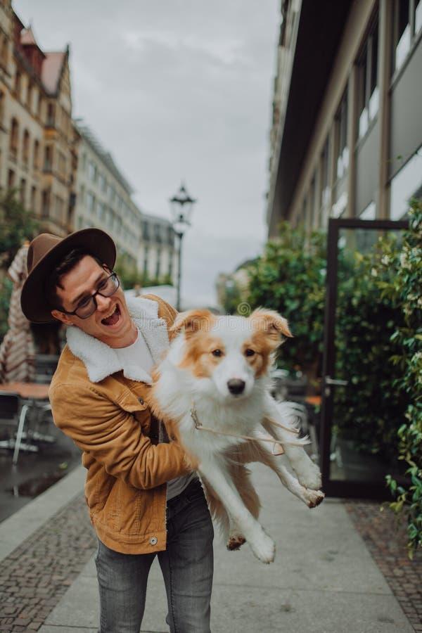 El individuo de moda en un sombrero camina alrededor de Europa en la ciudad con su border collie rojo del perro imagen de archivo libre de regalías