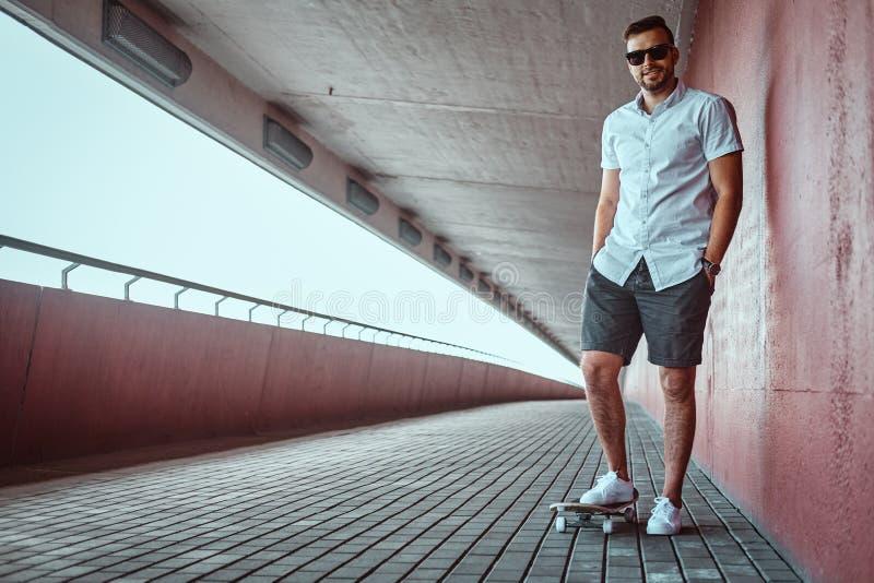 El individuo de moda hermoso sonriente del patinador en gafas de sol se vistió en una camisa blanca y los pantalones cortos, incl imagen de archivo