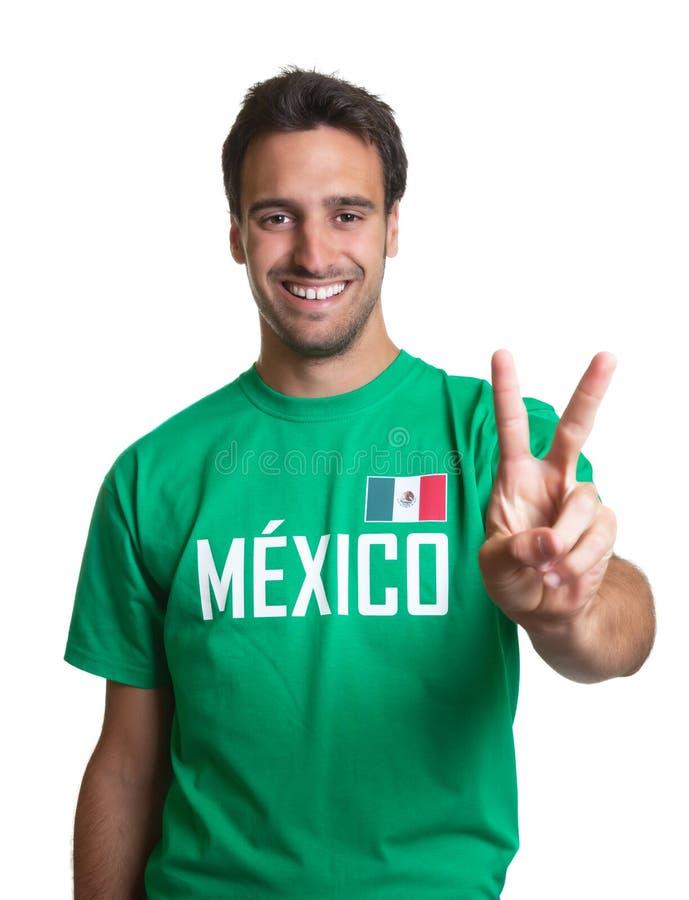 El individuo de risa en un jersey mexicano que muestra la victoria firma fotos de archivo