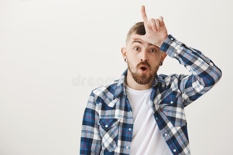 El individuo dio en el temptetion a la hermana falsa Retrato del hombre joven confiado apuesto en camisa y oído llanos azules imagen de archivo