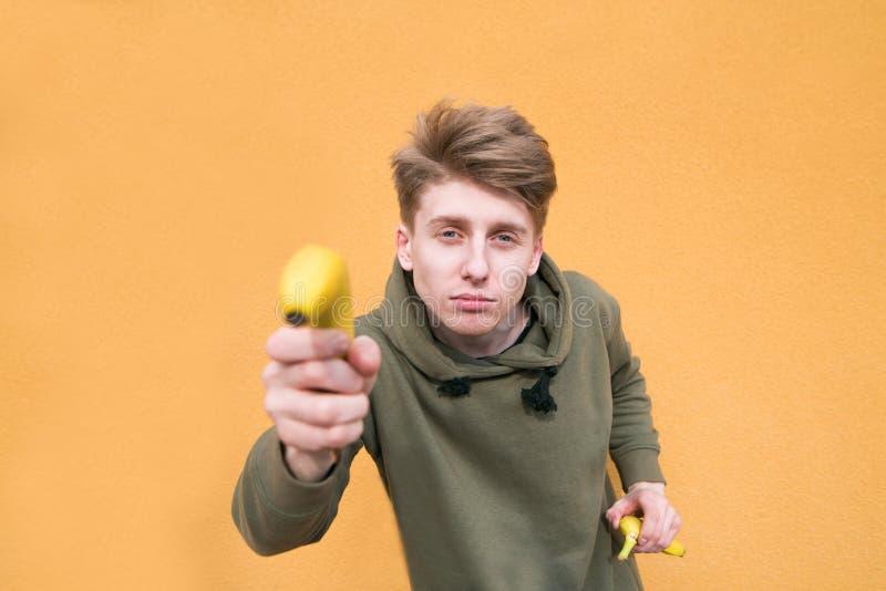 El individuo divertido celebra un plátano en sus brazos y miradas en la cámara Foco en un hombre joven fotos de archivo