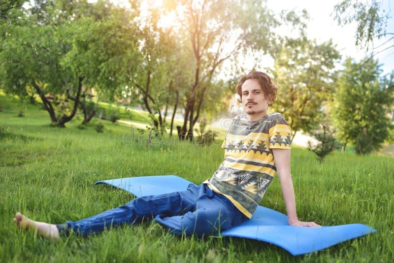 El individuo elegante hermoso disfruta de la naturaleza y de sueños sobre algo que se sienta en el parque Vista pac?fica imagenes de archivo
