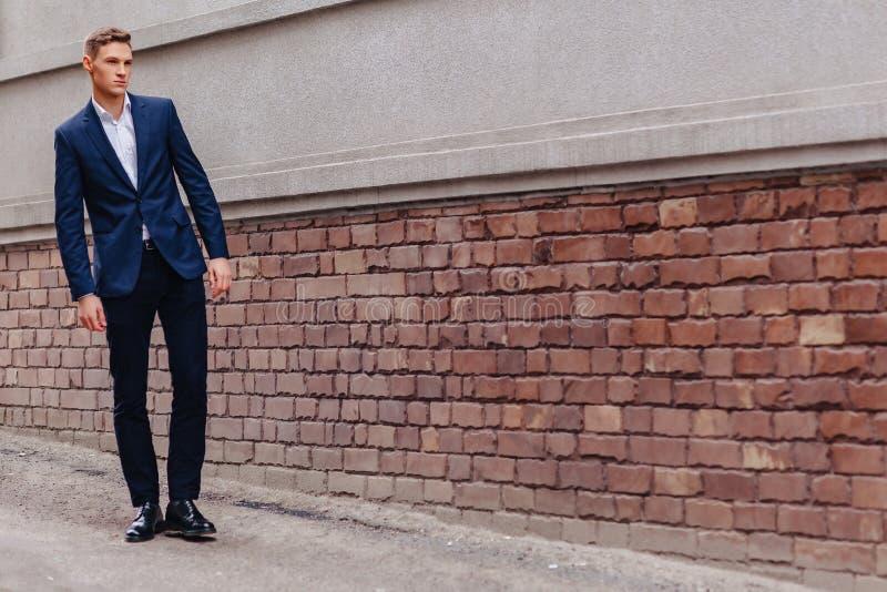 El individuo elegante joven con una cara monumental camina en una ciudad fresca cerca de las paredes de madera y de piedra imagen de archivo