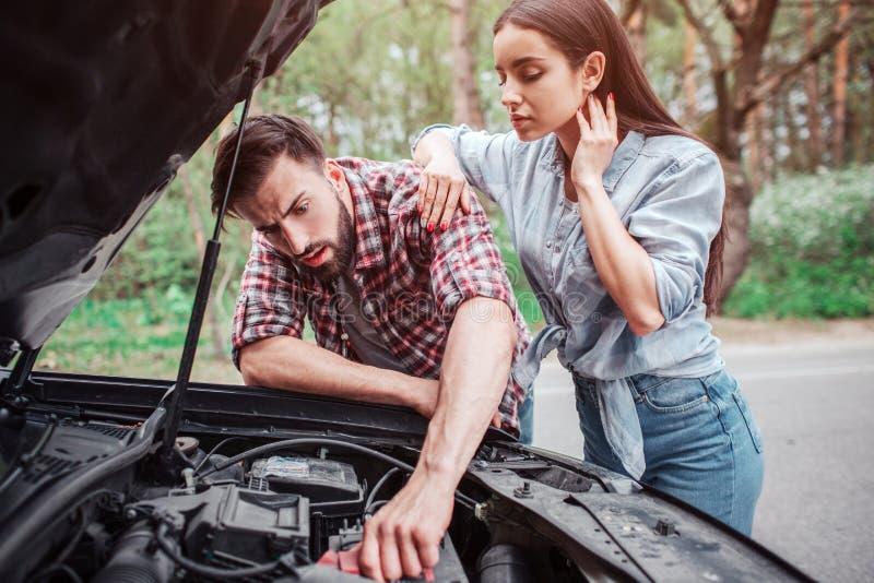 El individuo elegante y serio está fijando el coche La muchacha se está colocando además de él y está mirando al proceso Ella se  foto de archivo libre de regalías