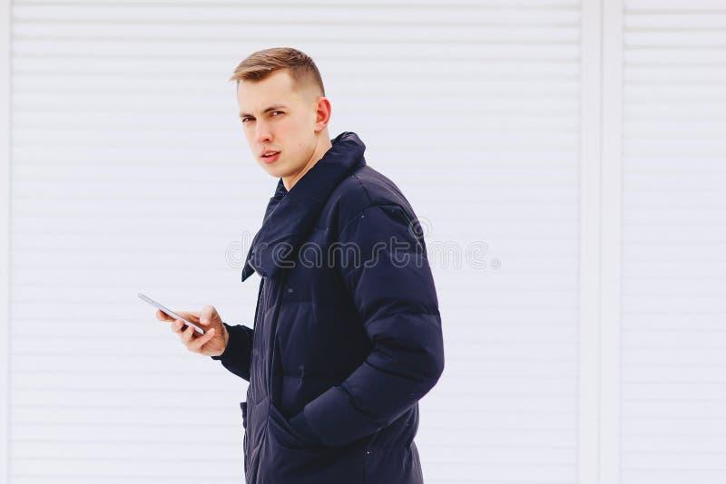 el individuo en chaqueta del invierno escribe SMS fotografía de archivo libre de regalías