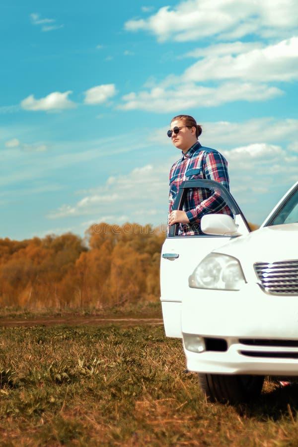 El individuo en gafas de sol fuera del coche imagen de archivo