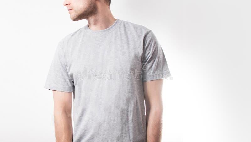El individuo en la camiseta gris en blanco, soporte, sonriendo en un fondo blanco, mofa para arriba, espacio libre, logotipo, dis fotos de archivo