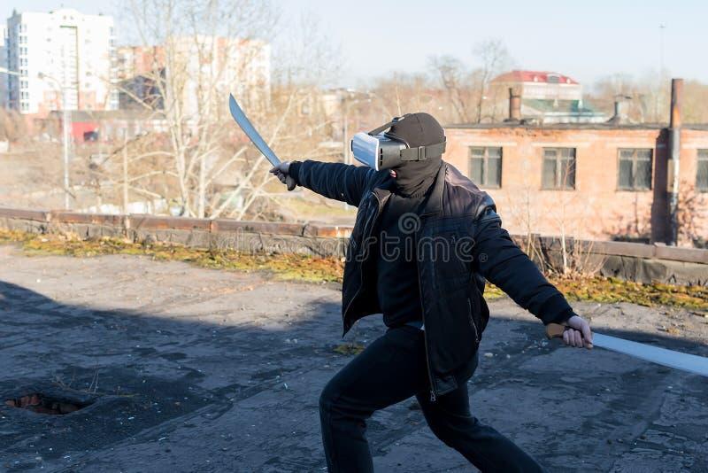 El individuo en la máscara, la chaqueta de cuero y los vidrios de la realidad virtual imagen de archivo