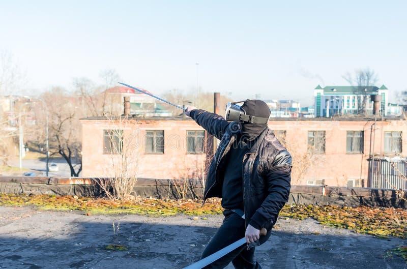 El individuo en la máscara, la chaqueta de cuero y los vidrios de la realidad virtual fotografía de archivo libre de regalías