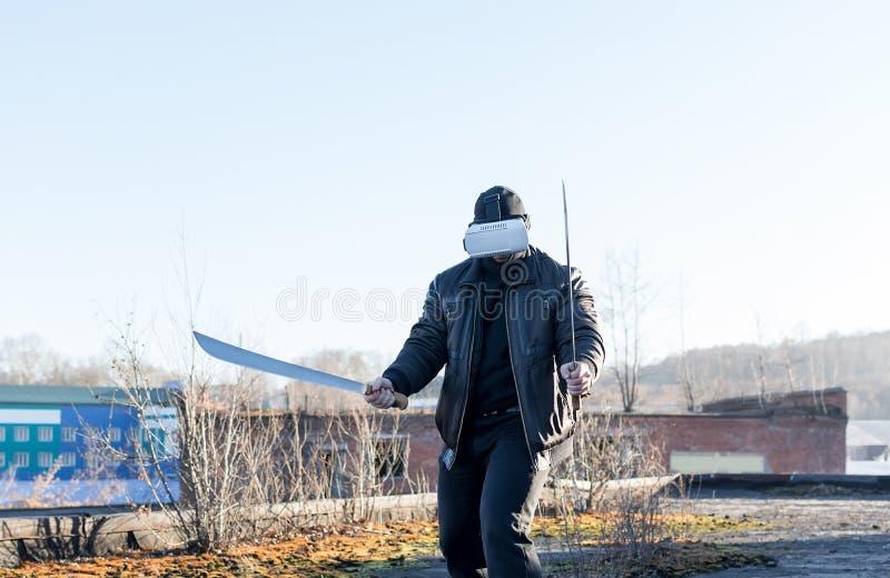 El individuo en la máscara, la chaqueta de cuero y los vidrios de la realidad virtual foto de archivo libre de regalías