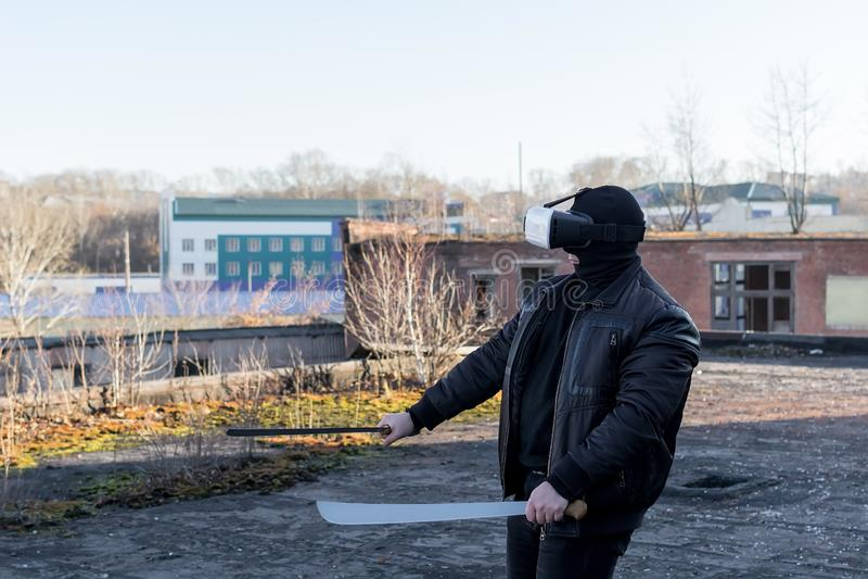El individuo en la máscara, la chaqueta de cuero y los vidrios de la realidad virtual fotos de archivo