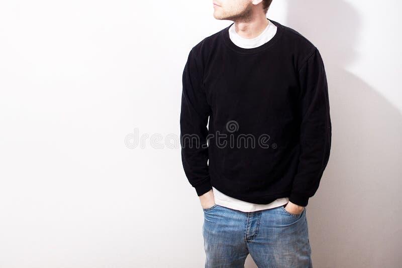 El individuo en la sudadera con capucha negra en blanco, camiseta, soporte, sonriendo encendido fotos de archivo libres de regalías
