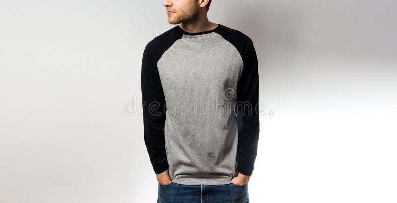 El individuo en el negro gris en blanco, camiseta, soporte, sonriendo en un fondo blanco, mofa para arriba, espacio libre, logoti imagen de archivo libre de regalías