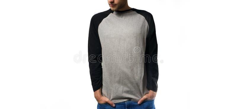 El individuo en el negro gris en blanco, camiseta, soporte, sonriendo en un fondo blanco, mofa para arriba, espacio libre, logoti fotografía de archivo libre de regalías