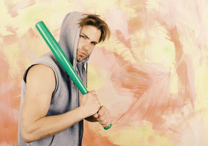 El individuo en sudadera con capucha sin mangas gris sostiene el palo verde claro, espacio de la copia Deportes y concepto de la  fotos de archivo libres de regalías