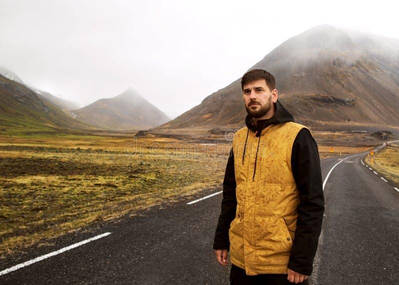 El individuo en una capa amarilla está caminando abajo del camino en las montañas, foto de archivo libre de regalías