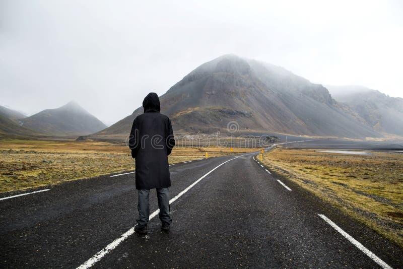 El individuo en una capa amarilla está caminando abajo del camino en las montañas, fotografía de archivo