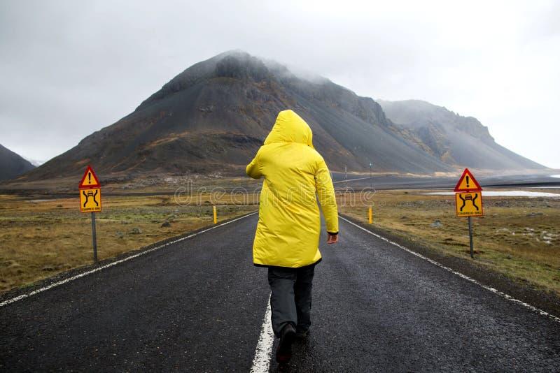 El individuo en una capa amarilla está caminando abajo del camino en las montañas, imagenes de archivo