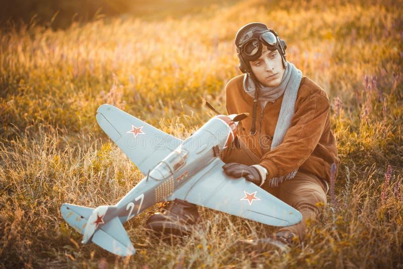 El individuo en vintage viste al piloto con un modelo del aeroplano al aire libre foto de archivo libre de regalías