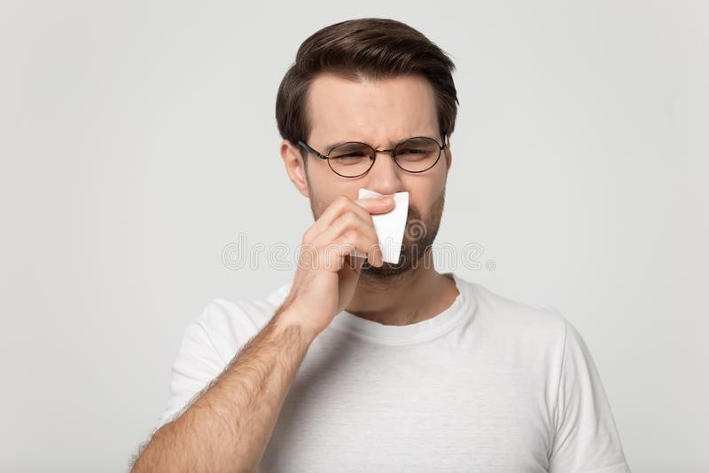 El individuo enfermo que estornuda limpiando la nariz o sufre de olor desagradable fotografía de archivo