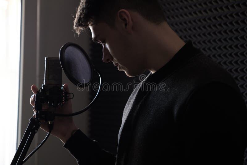 El individuo está inclinando su cabeza delante del micrófono que la lleva a cabo con una mano, la foto del lado fotos de archivo