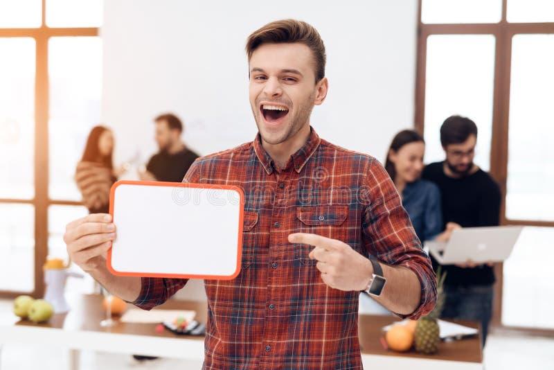 El individuo está llevando a cabo a un tablero blanco foto de archivo
