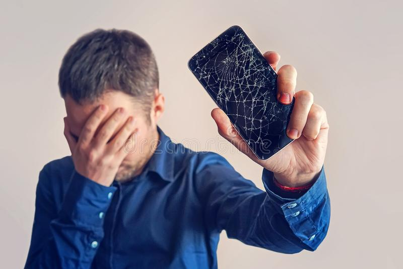 El individuo está sosteniendo un smartphone negro con una exhibición quebrada imagen de archivo
