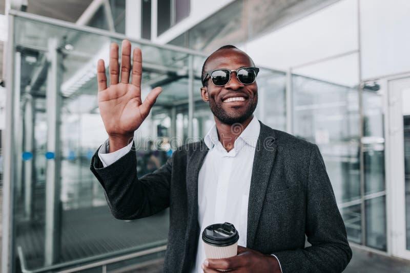 El individuo feliz está gozando del café fuera del aeropuerto imagen de archivo