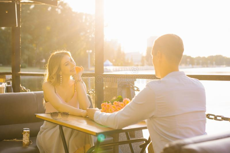 El individuo feliz y las manos de la sonrisa y del control de la muchacha, miran uno a la tabla del café del verano la puesta del foto de archivo libre de regalías
