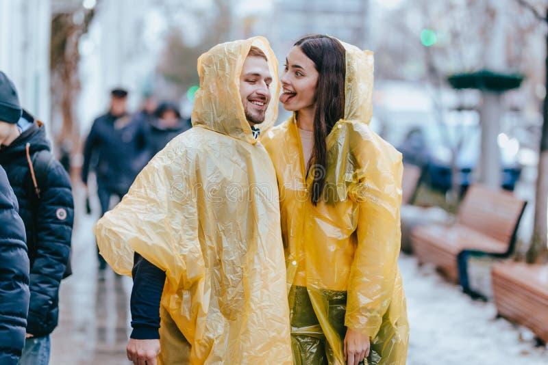 El individuo feliz y su la novia vestidos en impermeables amarillos est?n caminando en la calle bajo la lluvia fotografía de archivo libre de regalías