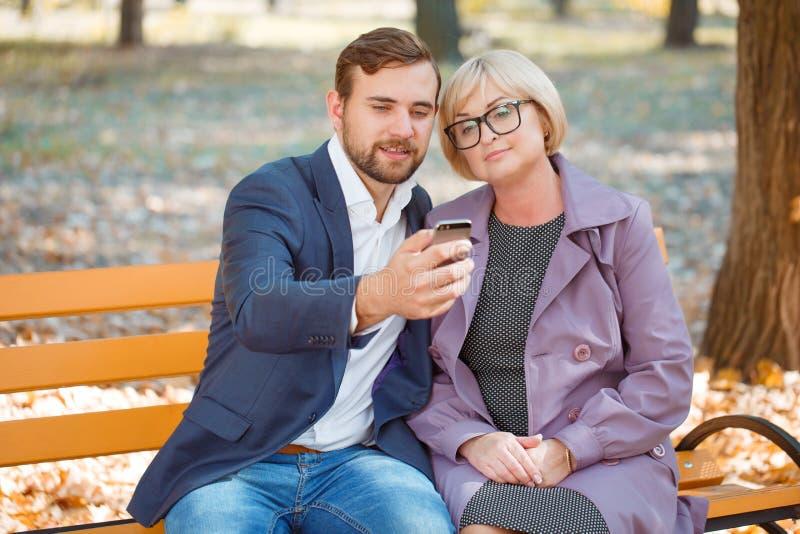 El individuo hace el selfie con su madre en el banco en parque del otoño fotos de archivo libres de regalías