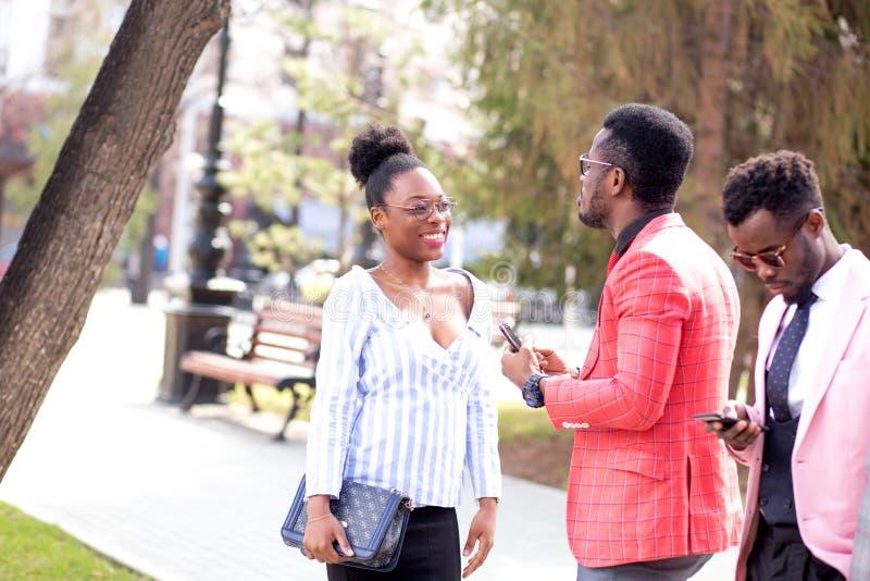 El individuo hermoso de la moda está hablando de sus sensaciones a la muchacha hermosa africana imagenes de archivo