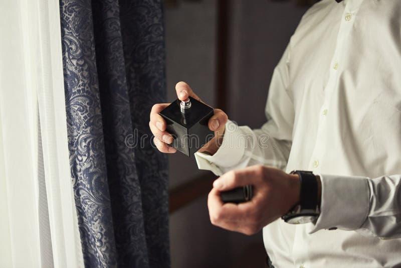 El individuo hermoso está eligiendo los perfumes, hombre elegante en traje usando cologne, novio que consigue listo por la mañana imagen de archivo