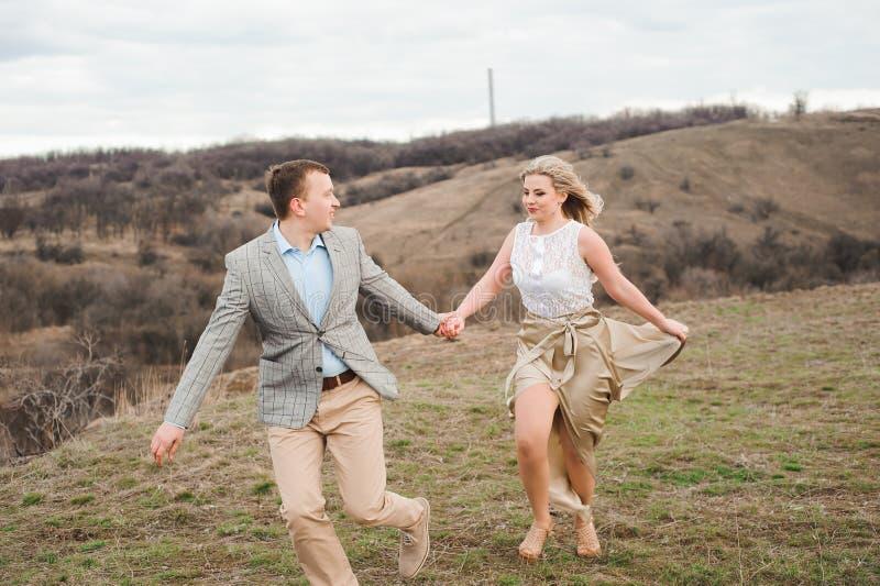 El individuo hermoso y la muchacha rubia que caminan en el campo, un hombre lleva a una mujer que lleva a cabo la mano imagen de archivo libre de regalías